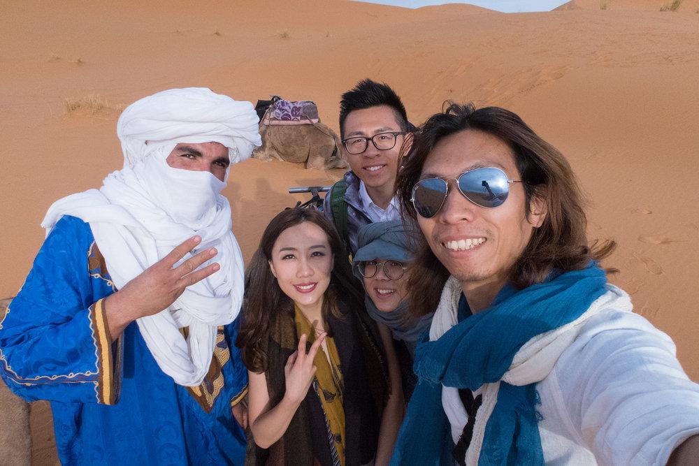 """完成沙漠第一天的拍攝,來張大合照!=)  後記: 今次再次到來到摩洛哥雖然來匆匆去匆匆,因為我們只拍攝了進入沙漠的一段三日兩夜行程,沒有在馬拉喀什或其他城市拍攝雖然有點可惜。期待下次拍攝可以有更充足的時間休息一下,再四處走走看看,玩玩沙漠四驅車。 還記得兩年前第一次計劃到摩洛哥拍攝時,首先很擔心的便是到底這個國家安全嗎?因為伊斯蘭教國家感覺總好像會跟恐佈份子連在一起,經過更多的資料搜集後和頭兩次經驗講我知,其實摩洛哥人很多都非常友善,也很熱心幫人。只是食物方面的確不太適合東方人口味。但也是一種特色,我個人最喜歡當地特產""""薄荷茶""""呢! 記得我們一到步尋找酒店位置時,也有不少當地熱心人士主動幫我們帶路,我們反而非常擔心會被騙,很緊張似的,結果當然不是吧。只是我們城市人太多戎心,反而會看起來四周的人都像壞人一樣,真的需要反思一下了。"""