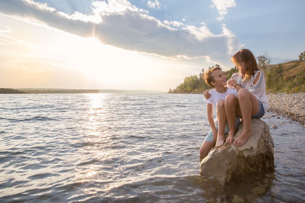 calgary family photography two kids sitting on a rock in a lake