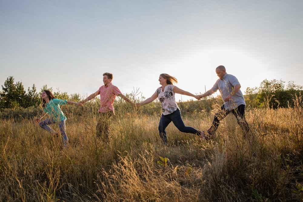 calgary family photography holding hands running and laughing