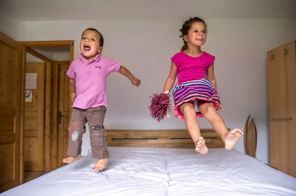 calgary family photography kids jumping on the bed