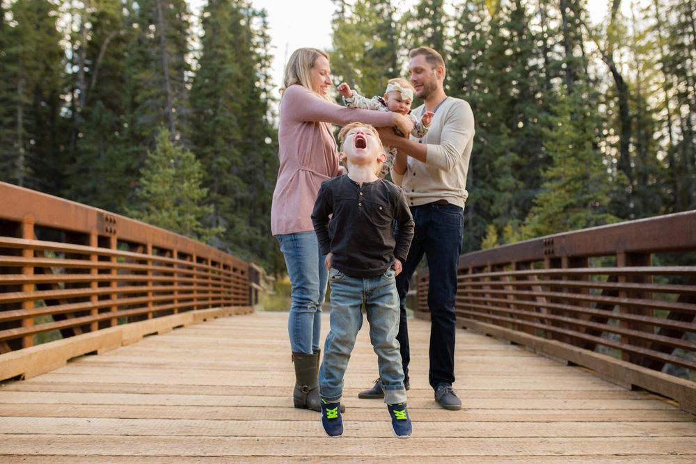 bridge, little boy jumping, pink wrap jacket, family photography