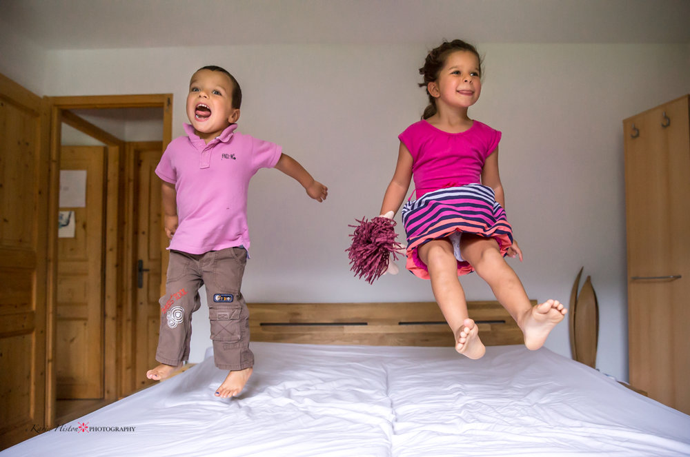 two kids jumping on the bed and playing around in pink clothes | Calgary child photographer