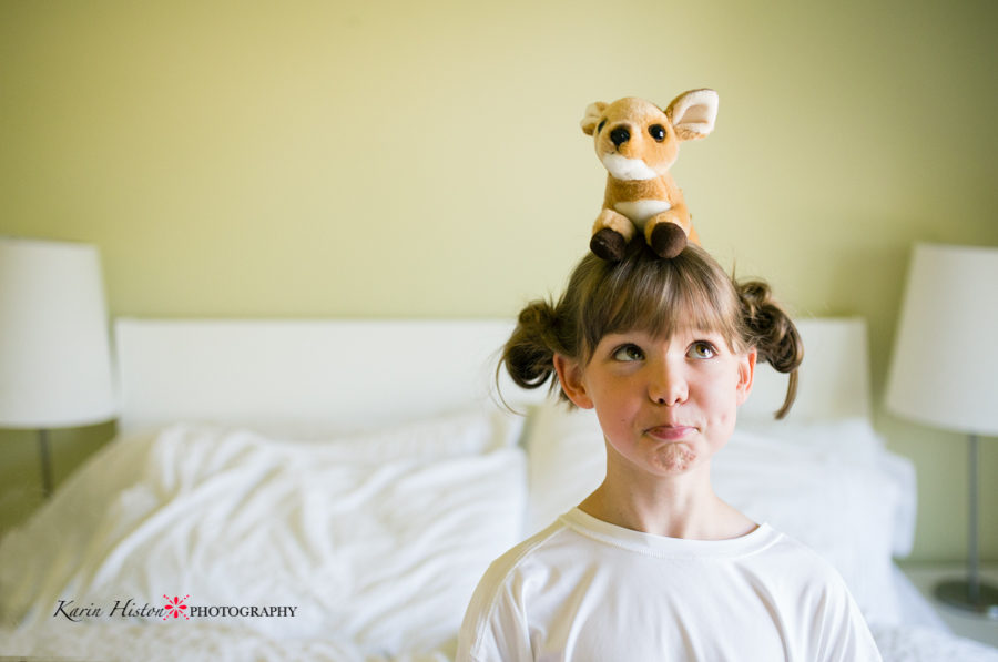 Girl with a stuffy on her head and silly face | Calgary child photographer