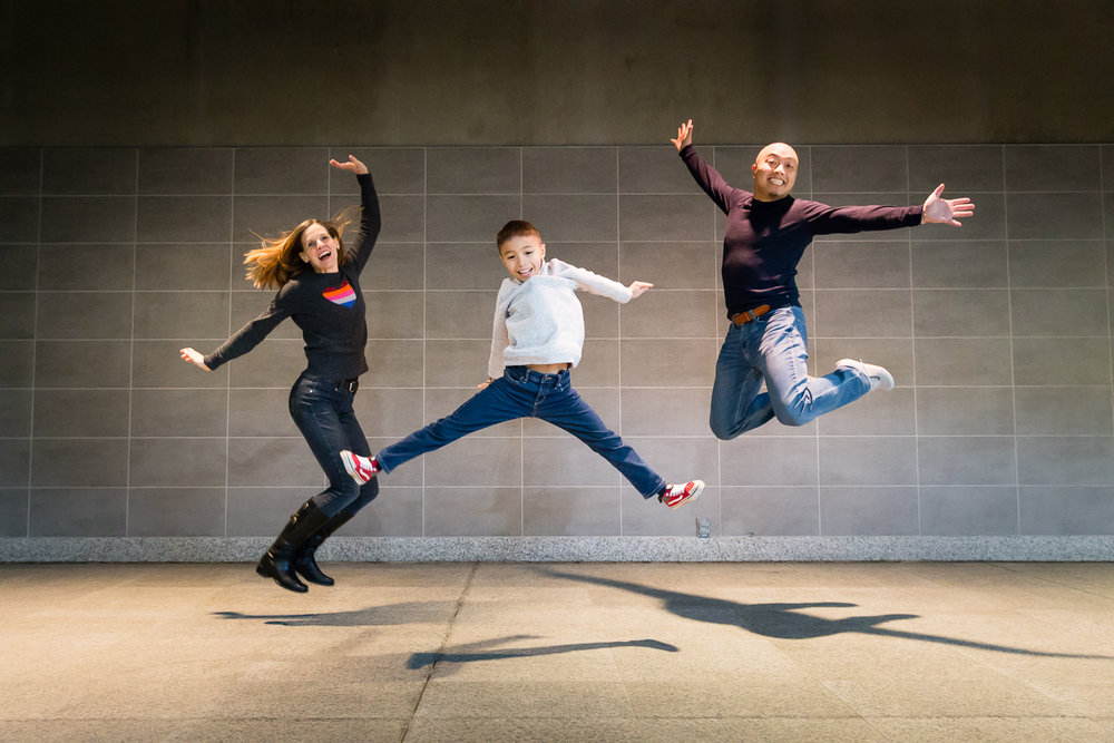 a family of three jumping together with a brick wall behind them | Calgary family photographer