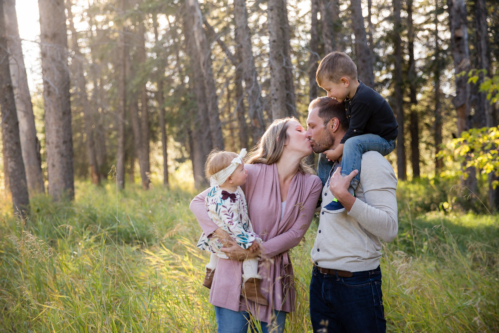 mom and dad kissing with two young kids in a green field | Calgary family photographer