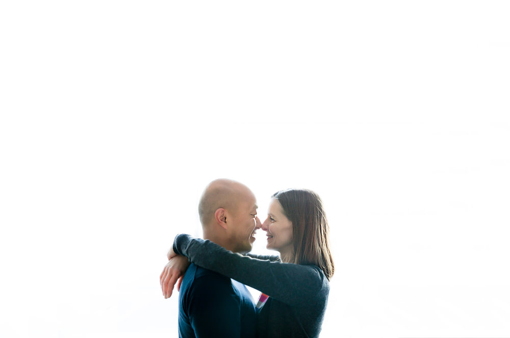 a couple facing one another nose to nose with white background | Calgary family photographer