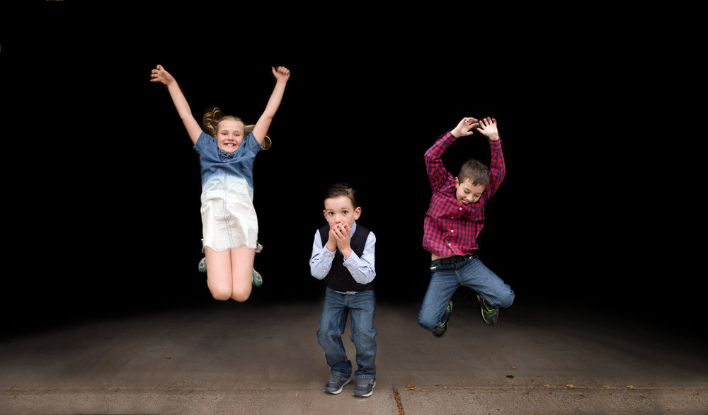 three children on pavement, two jumping and one covering his mouth