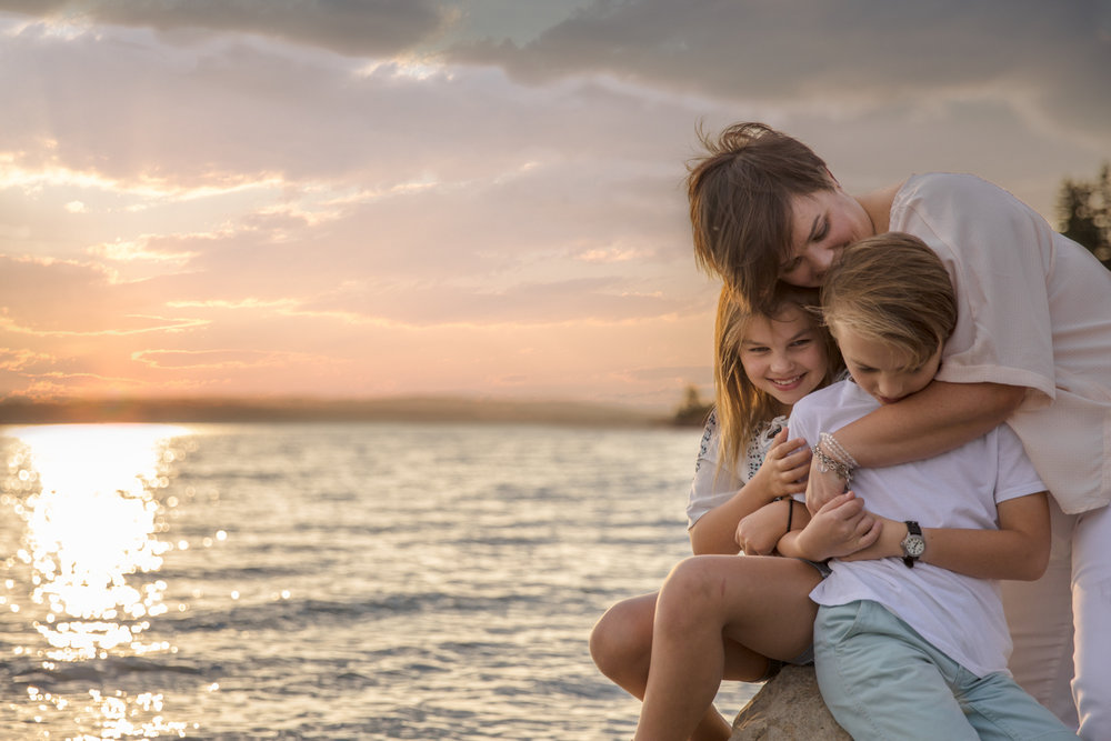 a mother with her two kids at the lake at sunset | Calgary family photographer