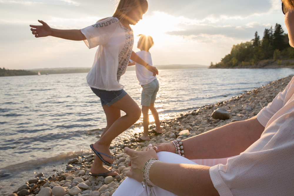 a child playing at a lake in the sunset with mom watching on | Calgary family photographer