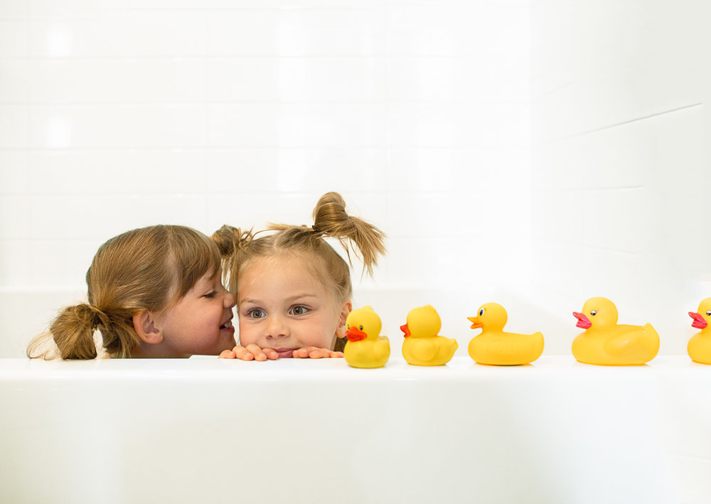 two kids in a tub with a line of ducks beside them | Calgary child photographer