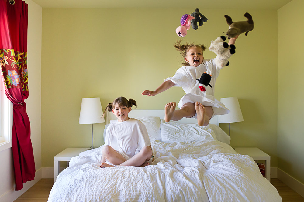 two kids jumping on the bed with stuffs in the air | Calgary child photographer