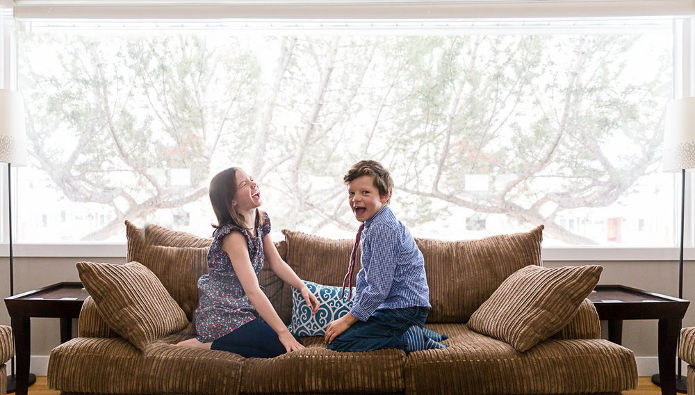 two kids facing each other on the couch and laughing | Calgary child photographer