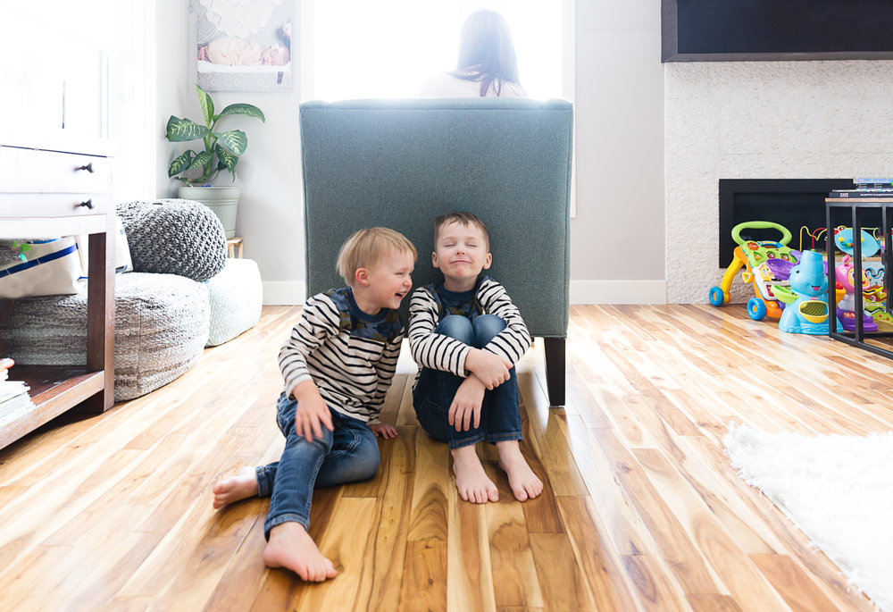 Boys giggling behind a chair with mom sitting in it