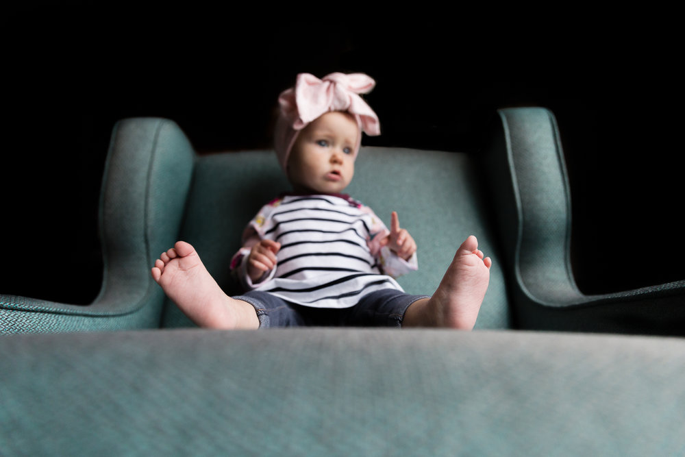 baby sitting on a green chair toes