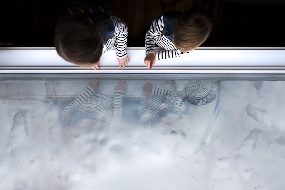 two boys at the window looking out at the snow