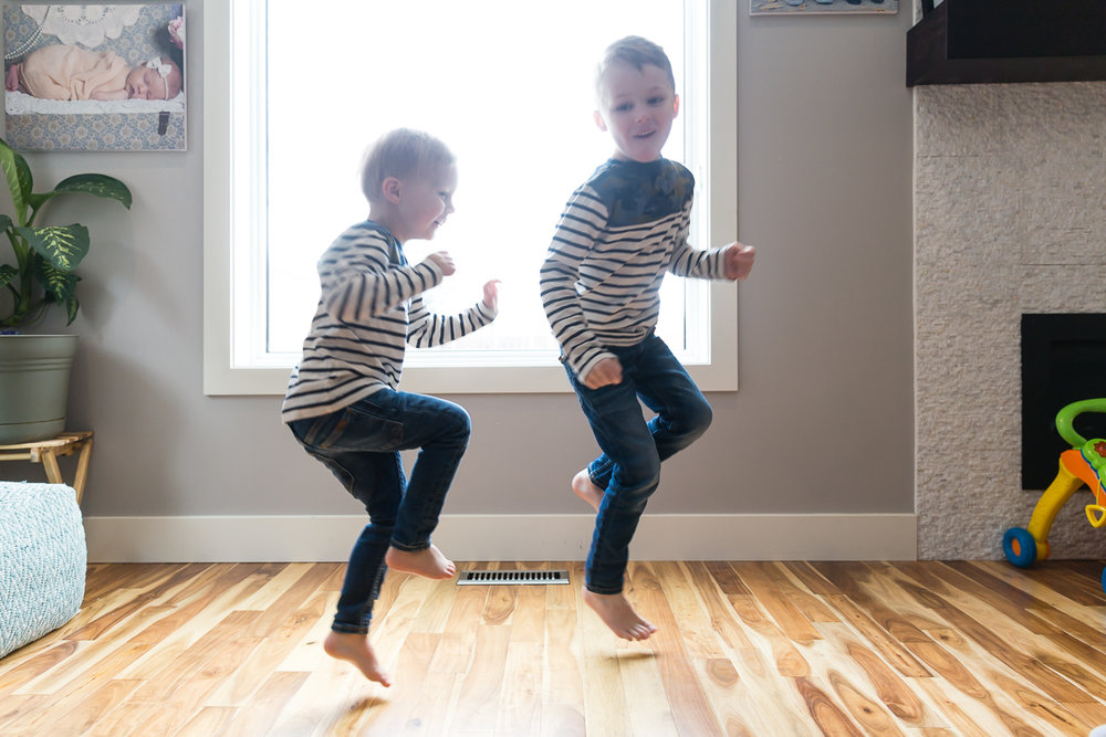 two boys playing and jumping in the light of a window