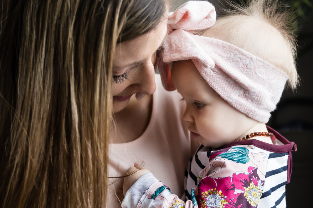 mom with her baby holding her hair with pink bow
