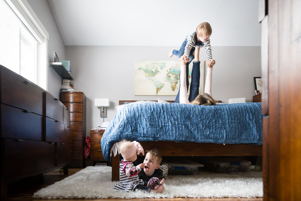 mom and boy playing airplane in bedroom