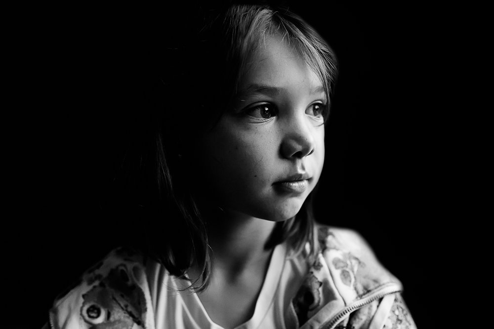 Black and white image of a girl looking out a window