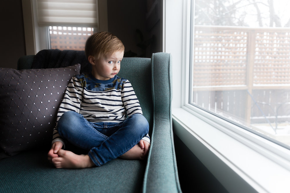little boy looking out a window sitting on green chair