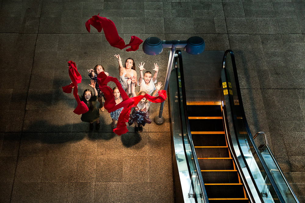 Girls with red scarves that are thrown into the air