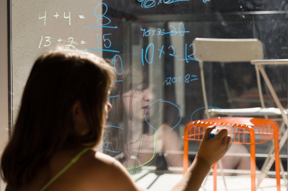 child writing math on window
