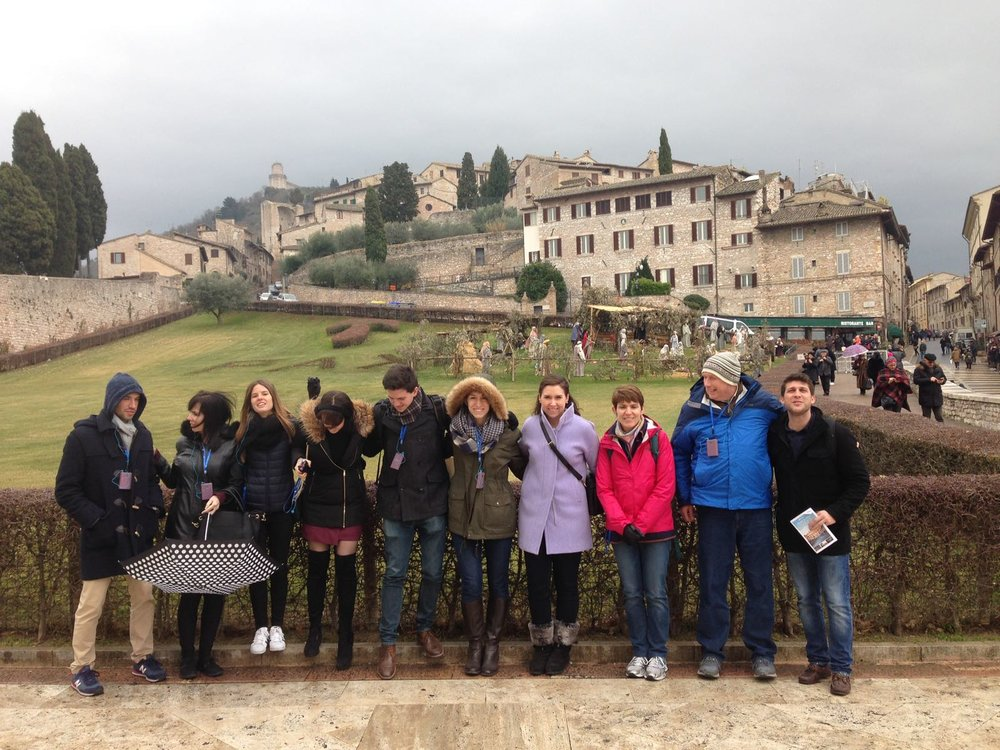 Pilgrims pause for a group shot in the rolling tuscan hills of Assisi, Italy.
