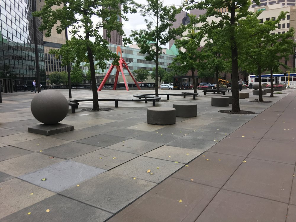 Plaza in Minneapolis with seating, artwork, trees, and hardscape, but no visitors.