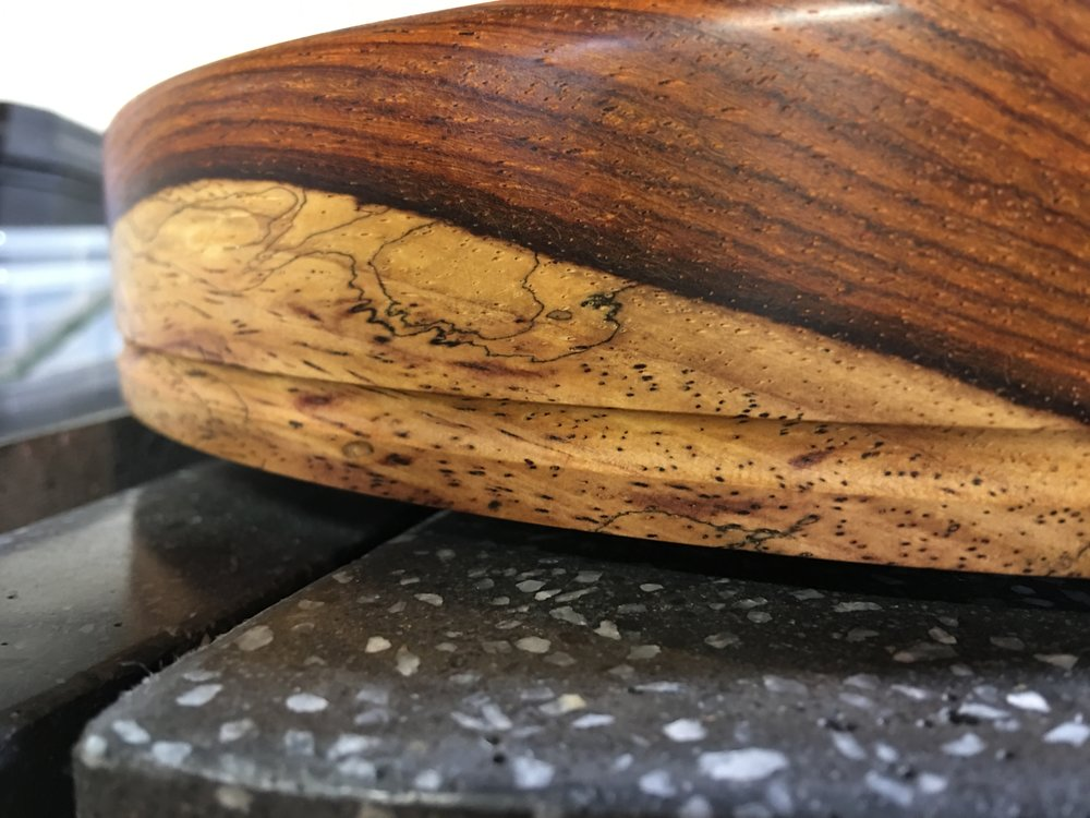 Here you can see the sapwood of the Cocobolo, which has a drastically different color than the deep red-orange heartwood. This is set atop the black plinth, which has its white aggregate exposed to create an almost stone-like texture. A groove is cut into the platter to keep the belt in place.