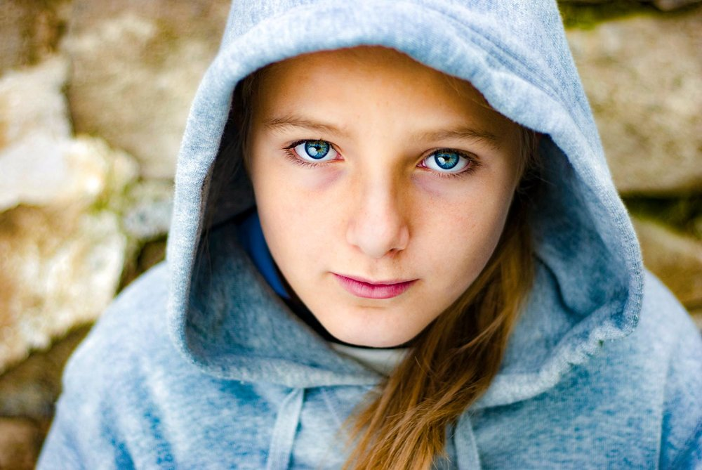 close up image of female teenager with hoody/sweatshirt looking at the camera