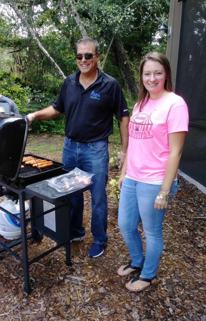 Prepping barbecue treats for the RAP House Back-to-School Carnival.  Left to right: Grillmaster Keith Mukherjee, VP of Central Programs, grilling hot-dogs, and standing beside him is Cayse Houston, RAP House Program Director.  This was an opportunity for RAP House temporary resident youth and staff to commingle on the lovely grounds of the shelter before the start of a new school year in Pasco County.