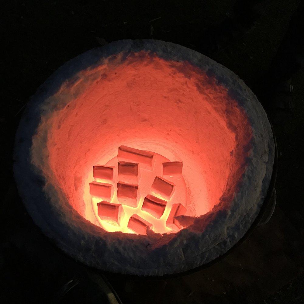 Raku Firing Houses….. the orangey glow of the kiln.