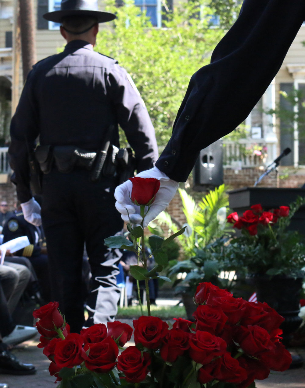 A police officer grabs a rose to add to the Fallen Officer Memorial in front of Savannah-Chatham police headquarters May 11, 2016, during a ceremony honoring law enforcement officers who died in the line of duty.  (Dash Coleman/Savannah Morning News)