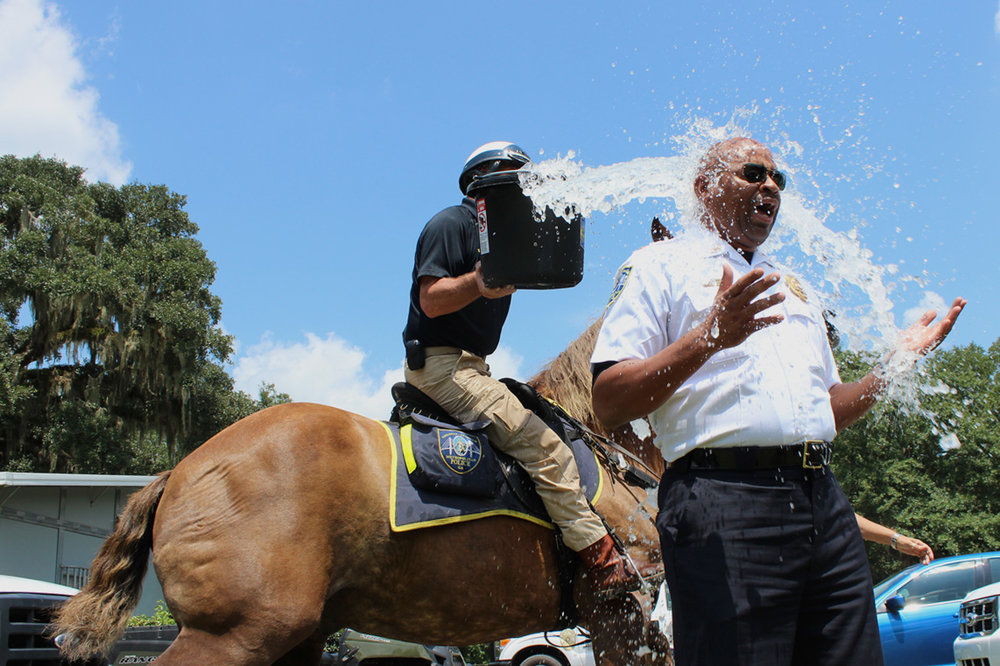 "A mounted patrol officer dumps cold water on Assistant Savannah-Chatham Police Chief Terry Enoch during the height of the ALS Association's ""ice bucket challenge"" in August 2014.  (Dash Coleman/Savannah Morning News)"
