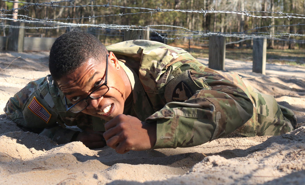 Spc. Cedric Thomas of the Georgia Army National Guard's 78th Aviation Troop Command crawls under barbed wire March 8, 2017, on Fort Stewart's obstacle course during the the state round of the Best Warrior competition.  (Dash Coleman/Savannah Morning News)