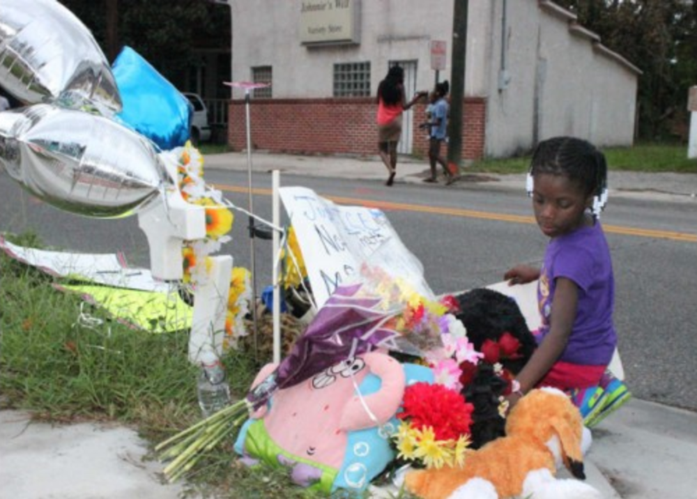 Nyasia Lewis, 6, kneels to add a sign to a roadside memorial for 29-year-old Charles Smith, who was shot and killed by Savannah-Chatham police after breaking free from a patrol car in September 2014.  (Dash Coleman/Savannah Morning News)