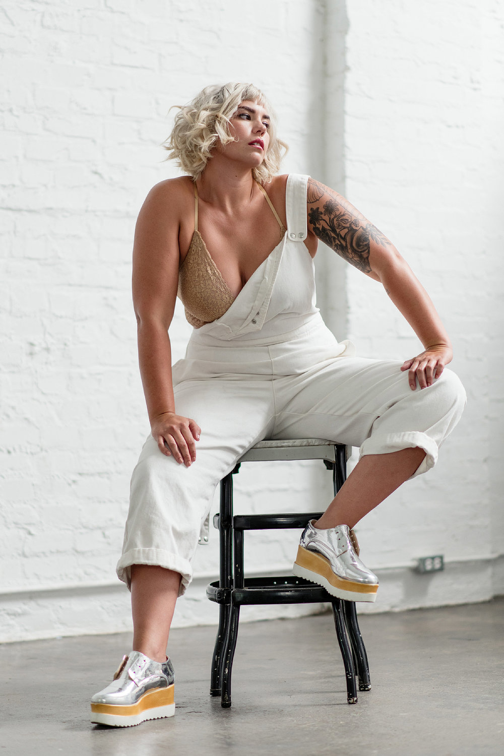 Blonde model with tattoo wearing silver oxfords sits on stool