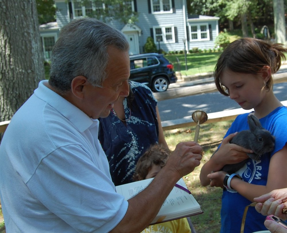 © JoAnn Kirkland photo Fr. Peter blesses a rabbit at the annual Blessing of the Pets in July