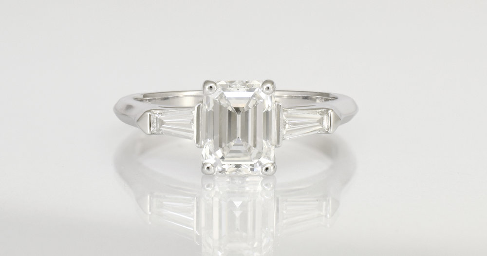 Emerald cut main diamond with tapered baguettes on the shoulders.