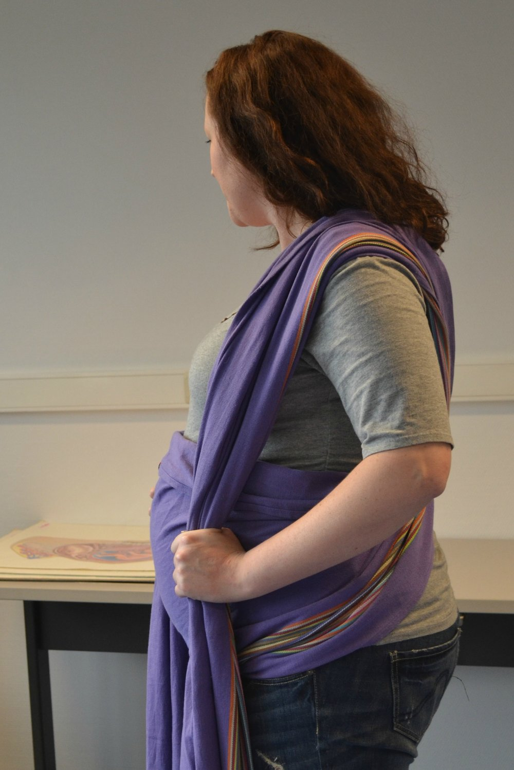 The rebozo wraps around the belly, crosses in the back and over the shoulders. Then, the mom can pull on the ends to help lift the belly, relieving some of the pressure on her growing belly.