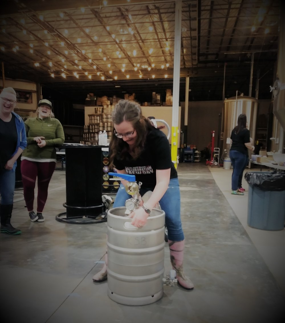 Kim is taking her turn mixing the yeast in the keg