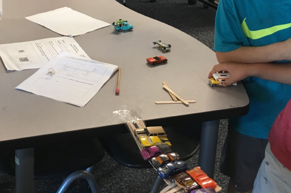 mustang makers work together to build a bridge from popsicle sticks and tape that is capable of supporting toy cars.