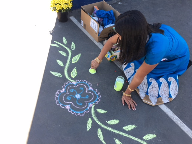 Nikita Ganatra creates rangoli sand art on the blacktop. Traditionally, rangolis are created outside of one's home to symbolize light, new beginnings, and the triumph of good over evil.