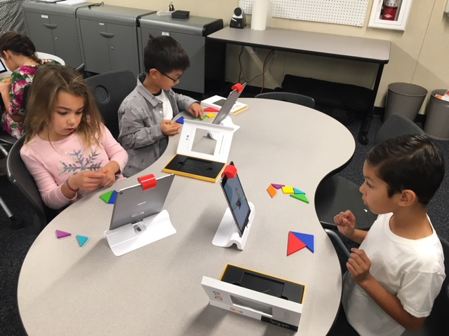 Students practicing their spatial awareness skills using osmo tangrams and manipulatives.