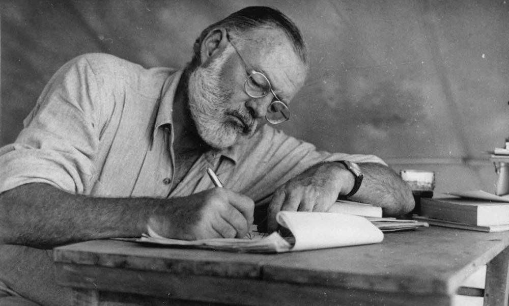 Commons-Ernest_Hemingway_Writing_at_Campsite_in_Kenya_-_NARA_-_192655-1500x902.jpg