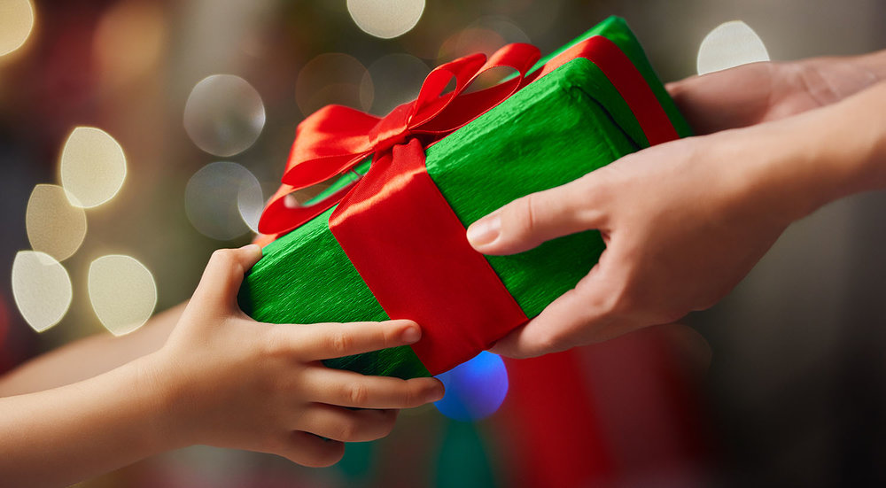 shutterstock_334282148-mother_child_giving_gift_Christmas-1500x826.jpg