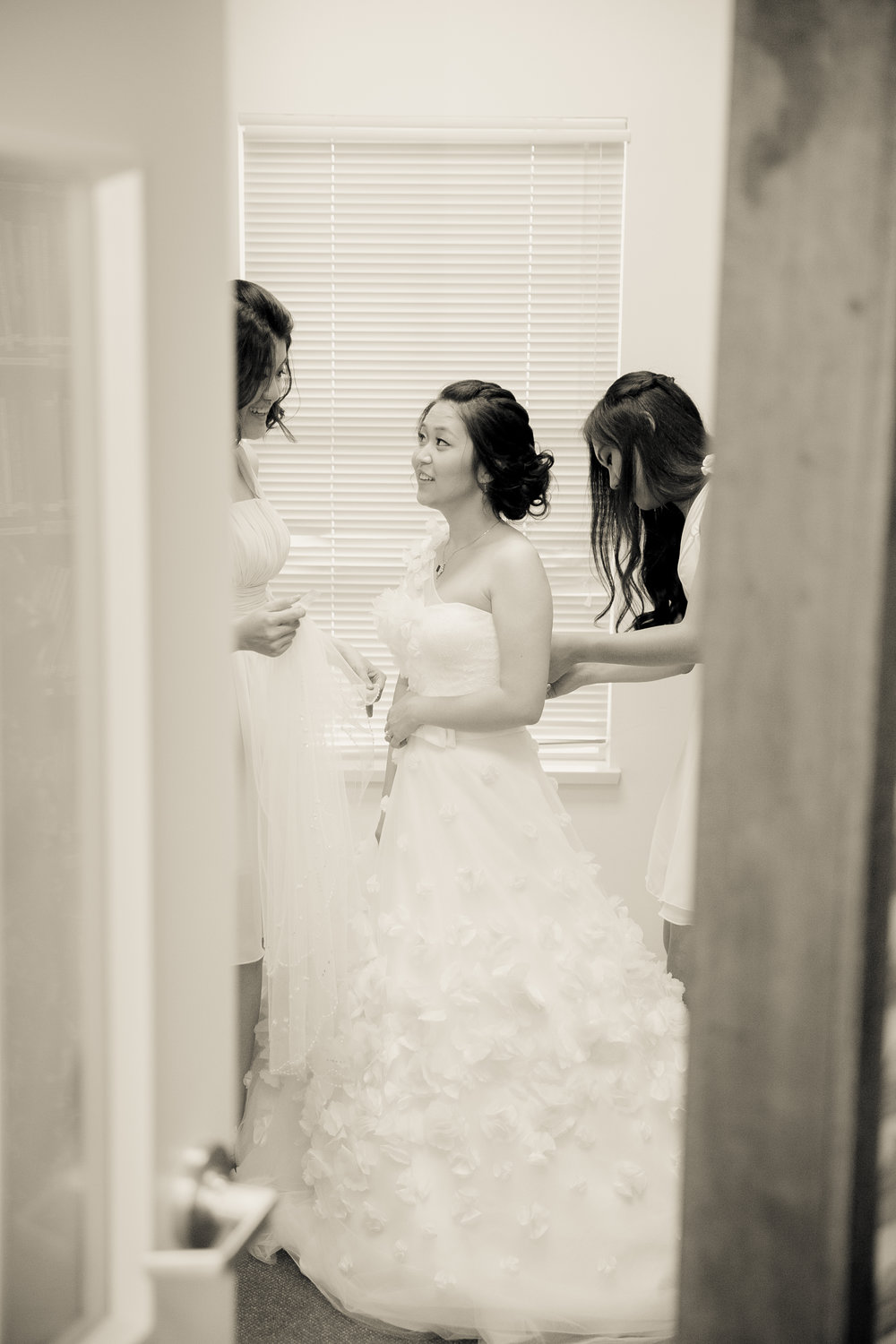 Bridesmaid tying the wedding gown for the bride