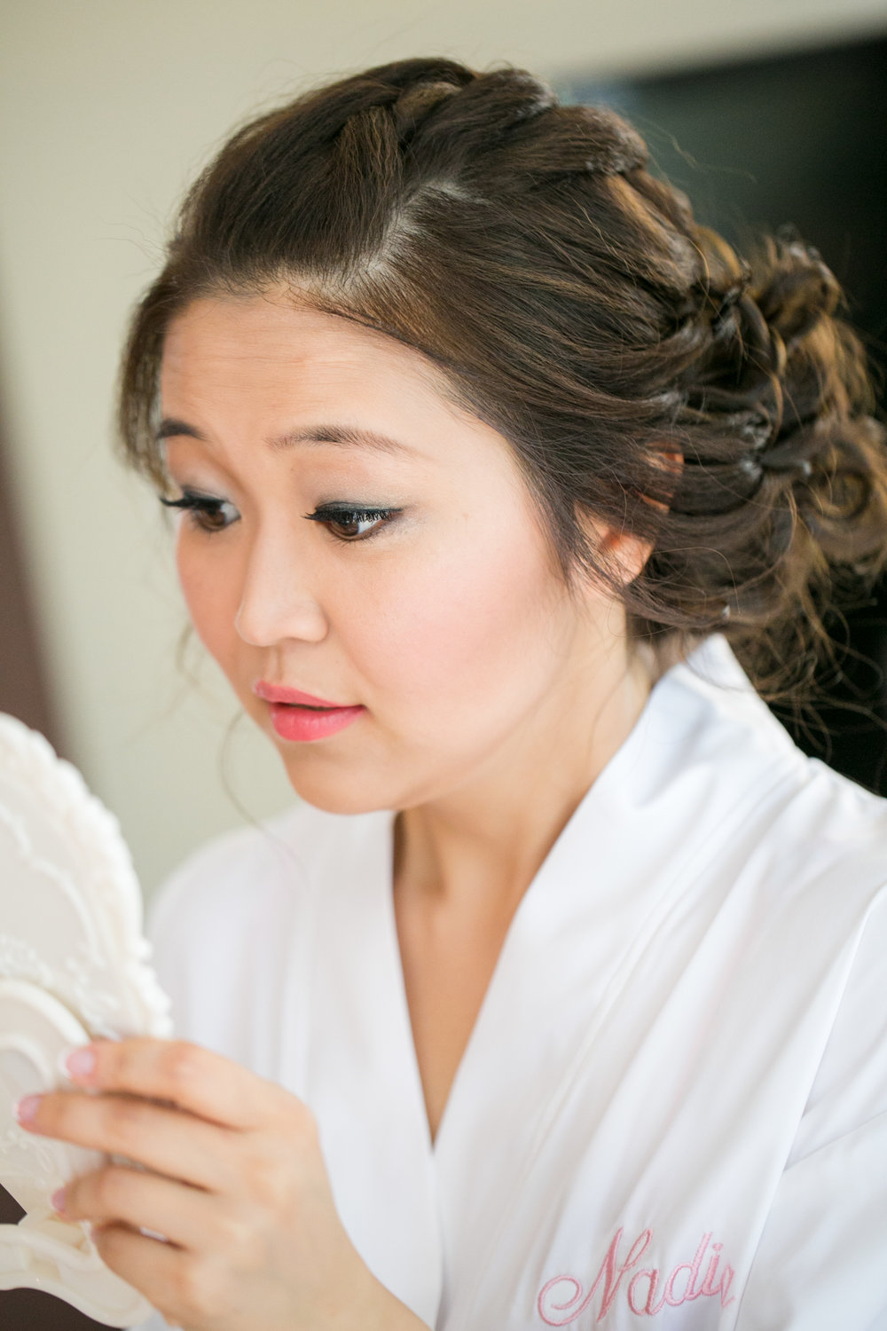 Bride checking makeup in mirror