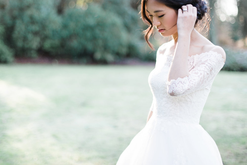 Ethereal bride tucking her hair behind her ear while walking in park