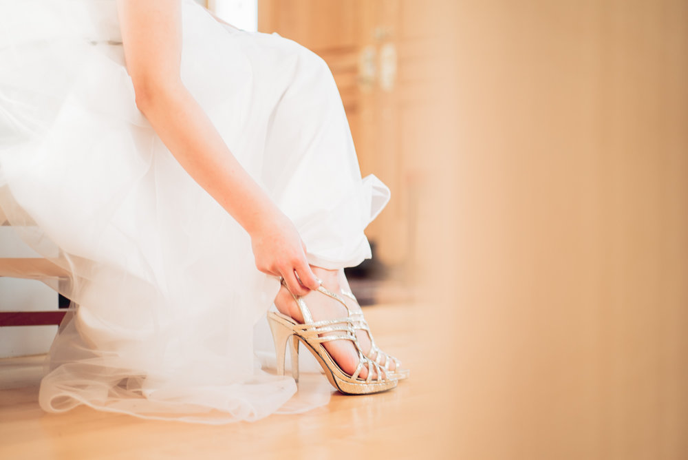 Bride puts on her shoe in her wedding dress